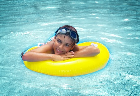 rubber ring: boy taking sunbath in pool on rubber ring, retro toned Stock Photo