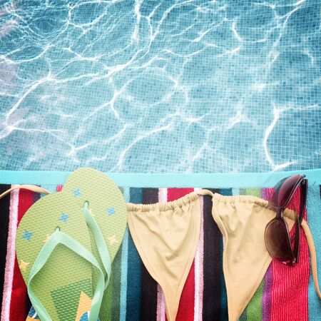 swimming suit: sandals ans swimming suit on towel border by poolside, retro toned
