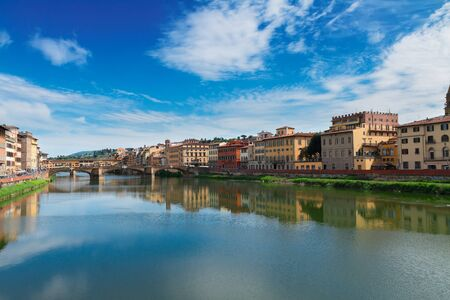 arno: famous bridge Ponte Vecchio reflecting in river Arno at summer day, Florence, Italy