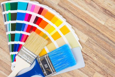 Color palette guide and brushes on wooden desktop