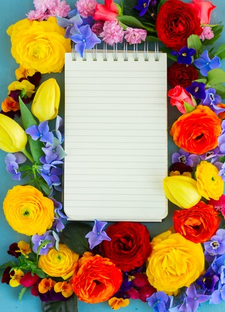 composition notebook: Flowers composition on blue wooden table with copy space on notebook Stock Photo