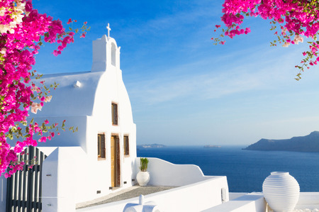 Bellos detalles de la isla de Santorini - casa típica con paredes blancas, flores de color rosa y azul del mar Grecia Foto de archivo - 57710608