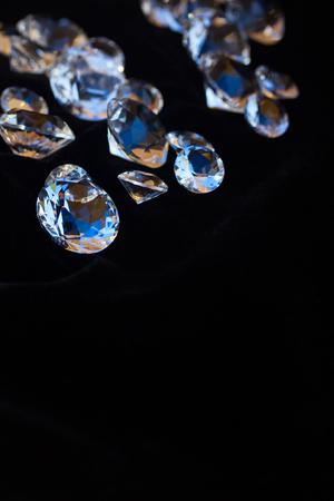 black velvet: Pile of shining diamonds on black velvet background with copy space, vertical shot