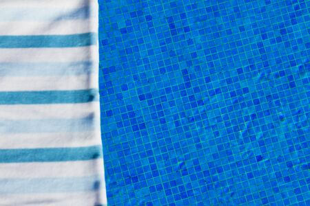 sripes: resort background with striped towel near pool side, focus on tiles