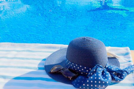 sripes: towel and summer hat near blue clear water of pool Stock Photo
