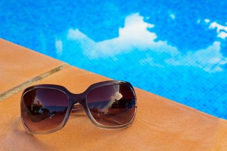 sripes: Sunglasses near blue tiled water of pool Stock Photo