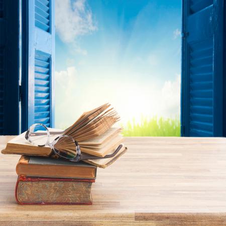 木桌桌上放着一堆书和玻璃,背景是蓝色的百叶窗