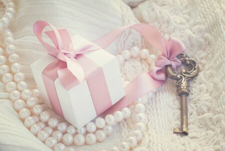 key box: gift box and key with pearl jewellery and white lace, retro toned Stock Photo