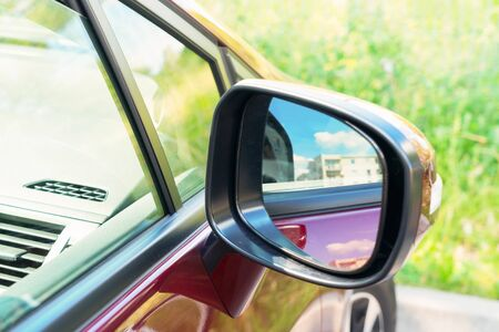 rearview: side rear-view mirror on a modern red car