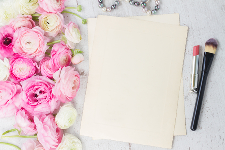 Pink and white ranunculus flowers with lipstick, makeup brush and empty paper note with copy space