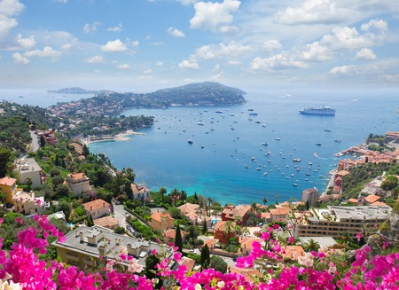 villefranche sur mer: lanscape of riviera coast, turquiose water, flowers and blue sky of cote dAzur at summer day, France Stock Photo