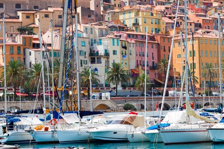 menton: colorful houses of Menton with yachts in old town, France