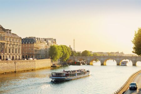 Pont Neuf and Seine river with tour boat at sunny summer sunset, Paris, France Stock Photo