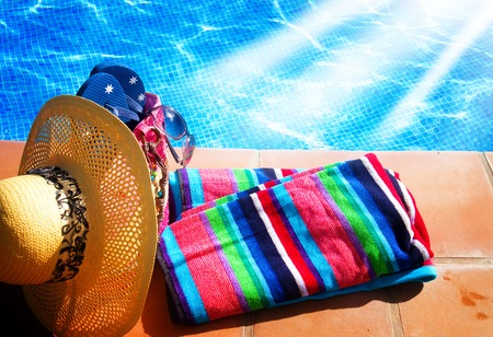 pool side: towel and bathing accessories near pool side with sun rays Stock Photo