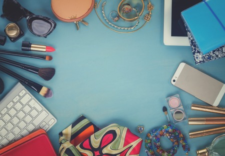 styled feminine desktop - woman fashion flat lay items on blue wooden background, copy space, top view, retro toned