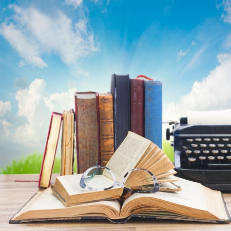 Old books, glasses and typewriter over sky and grass background - writting and publishing concept