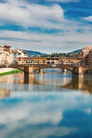 trinita: Ponte Santa Trinita bridge over the Arno River with cloudy sky and reflections, Florence, Italy
