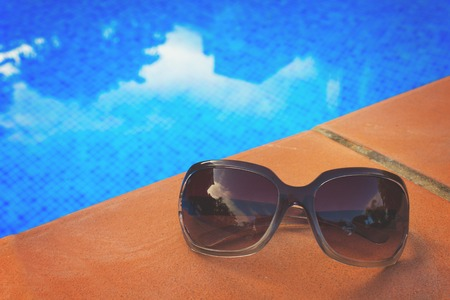 sripes: Sunglasses near blue tiled water of pool, retro toned