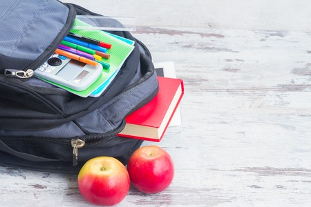 haversack: School backpack with supplies and apples on white desktop