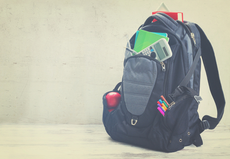haversack: School backpack with supplies on white desktop, retro toned