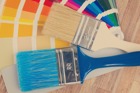 Color palette guide and brushes close up on wooden table, retro toned Stock Photo