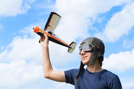 Teenager boy retro pilot playnig with toy plane Stock Photo