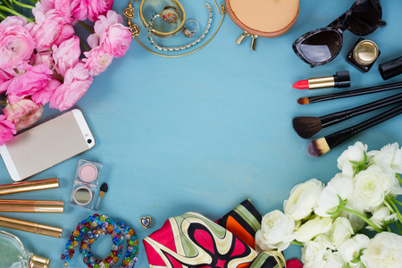 woman fashion flat lay items and fresh flowers on blue wooden background, copy space, top view Archivio Fotografico
