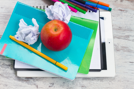 Apple with school supplies on white wooden table, top view