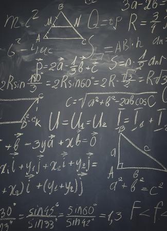 wiskundige formules geschreven in wit krijt op zwarte bord, verticale schot, retro afgezwakt