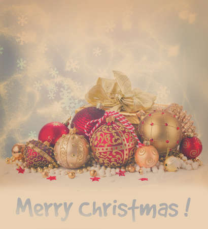 heap of snow: Heap of christmas balls in gold and red colors and gift box in snow isolated on white background, retro toned Stock Photo