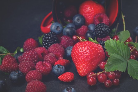 falling out: fresh berries falling out of red mug on black background, low key, retro toned