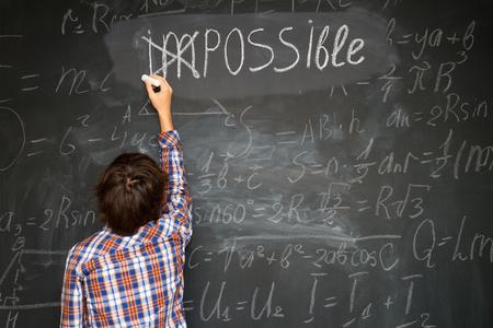 Junge, der ein Kreuz über unmöglich auf Tafel Standard-Bild