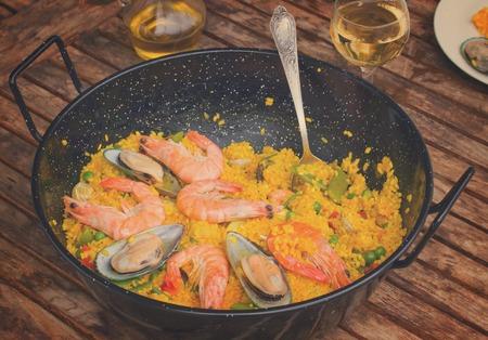 marisco: Seafood paella in black pan -traditional spanish rice dish, retro toned