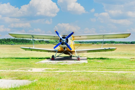 One vintage airplane in summer field under blue sky