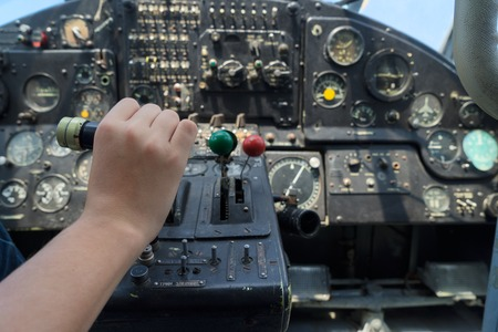 throttle: Vintage airplane dashboard with hand pushing leverer, shallow focus on hand