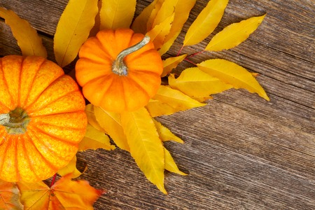 orange pumpkins with fall yellow leaves on wooden textured table, top view