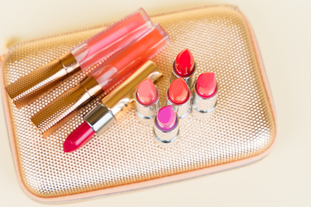 pursue: Collection of colorful lipsticks on golden woman pursue Stock Photo