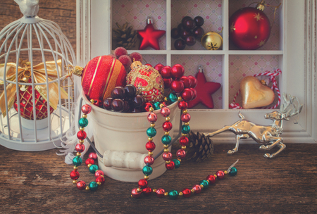 retro christmas: pot of christmas retro decorations on wooden table, retro toned