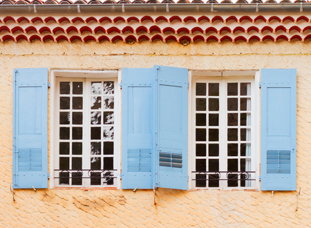 mediterranean culture: Windows with blue shutters, beautiful details of provencal typical small old town in Provence, France