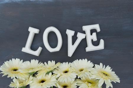 herbera: Beige gerbera flowers border on dark wood with love letters Stock Photo