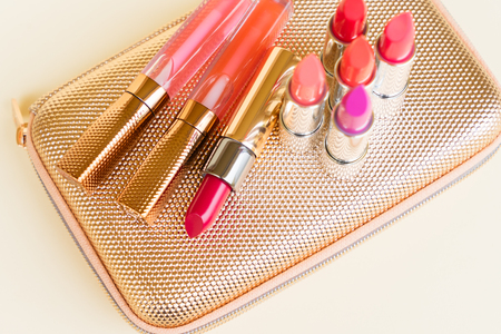 pursue: Collection of colorful lipsticks on golden woman pursue bag close up