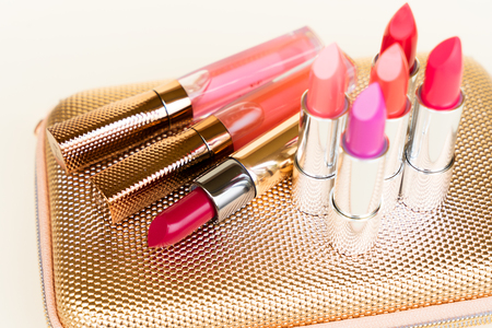pursue: Collection of colorful lipsticks on golden woman pursue bag