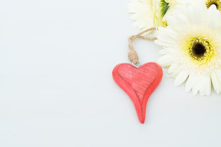herbera: Beige gerbera flowers with red heart for valentines day on gray wooden table