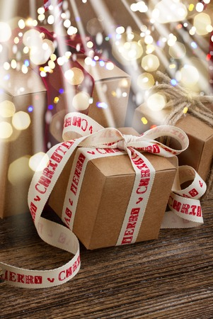 Handmade gift boxes on wooden background close up with glimming bokeh and light Stock Photo