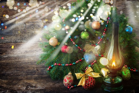 vintage glowing lantern with decorated christmas evergreen wreath on wooden background, low key with glimming lights Stock Photo