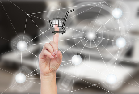 Mobile shopping concept - someones hand pointing on cart Stock Photo