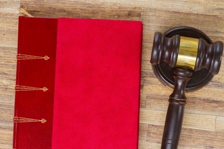 auctioning: Wooden Law Gavel and legal book on wooden desktop, top view