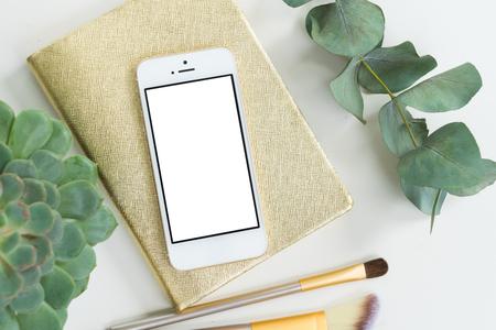 携帯電話アクセサリー黄金の女性とトップ フラット レイアウト スタイルを作られたシーンのモックアップを緑の植物、空の画面背景にコピー スペ