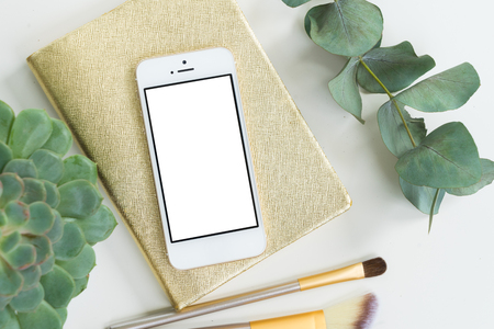 Phone with golden woman accessories and green plants mock up flat lay styled scene, top view, copy space on empty screen background