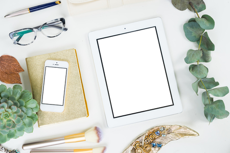 Tablet and phone with golden woman accessories and green plants mock up flat lay styled scene, top view, copy space on empty screen background